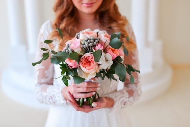 La novia joven sostiene el ramo rosado de la boda