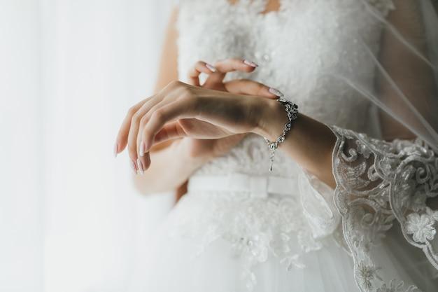 Novia con joyas a mano por la mañana en el día de la boda.