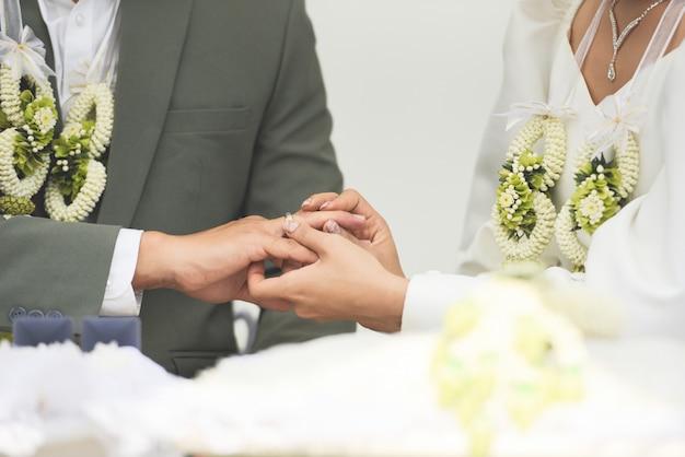 La novia lleva un anillo de bodas en el novio en el dedo anular de la mano derecha el día de su boda