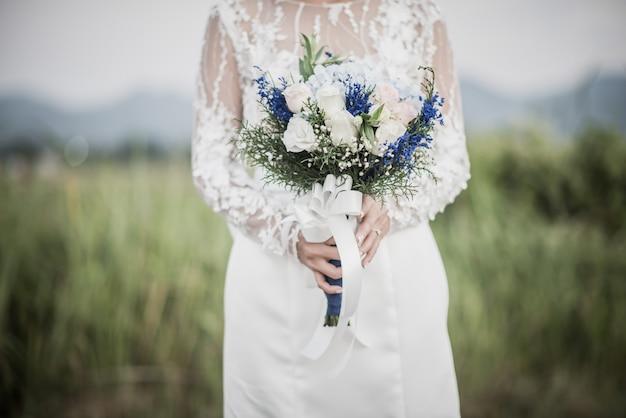 Novia mano que sostiene la flor en el día de la boda