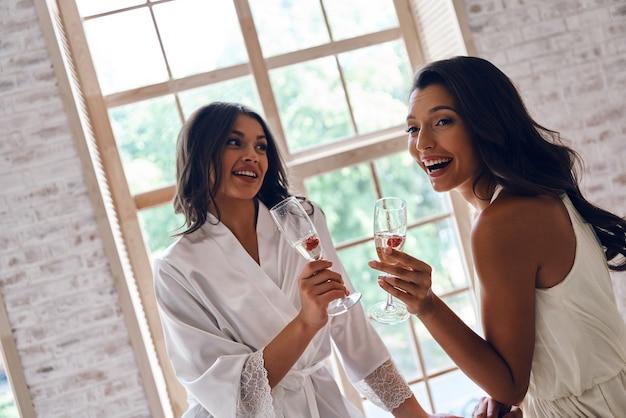 Novia con mejor amiga. dos atractivas mujeres jóvenes sonriendo mientras beben champán en el probador