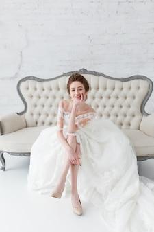 Novia mirando por la ventana, ella espera al novio sentado en el gran sofá clásico.