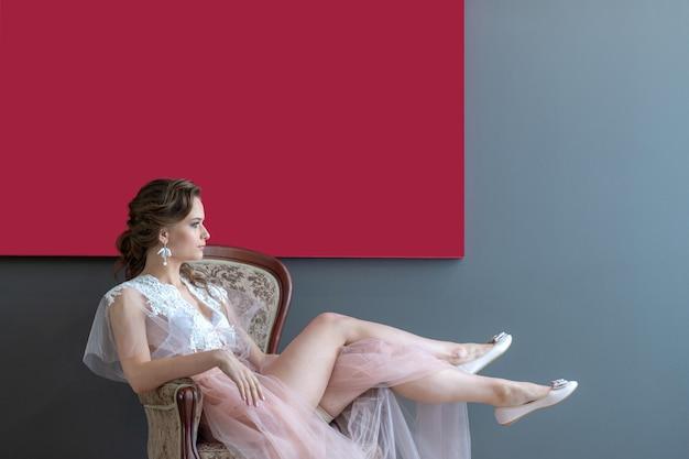 Novia de la moda siiting en silla en bata debajo de la imagen roja.