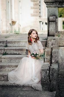 Novia modelo de moda joven con piel perfecta y maquillaje, fondo blanco. hermosa novia en las escaleras de fondo blanco. una mujer con un vestido largo y blanco está sentada en las escaleras.