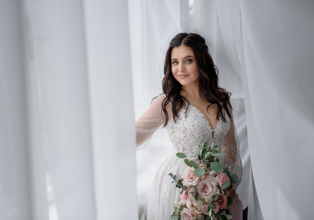 La novia morena bastante sonriente sostiene un tierno ramo de novia cerca de la ventana y mira directamente