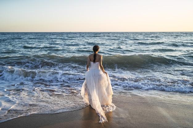 Novia morena caucásica acercándose al mar con un vestido de novia blanco