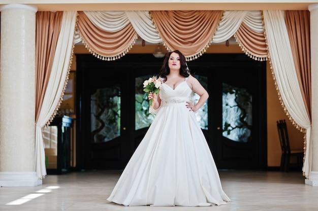 Novia morena de grandes pechos con ramo de novia presentado en cortinas de fondo de salón de bodas