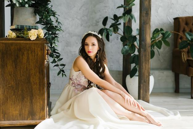 Novia morena hermosa en el vestido de boda que se sienta en el piso en el apartamento. ternura y juventud. día de la boda mañana