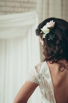Una novia morena con vestido desabrochado, una vista de cerca desde atrás