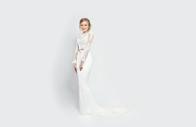 Novia mujer en vestido de novia largo blanco sobre un blanco