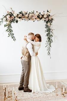 La novia y el novio se abrazan bajo un arco de flores