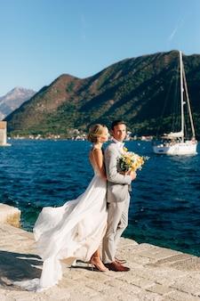 La novia y el novio se abrazan en el muelle de la bahía de kotor detrás de ellos