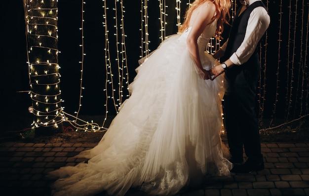 La novia y el novio se abrazan parados frente a la pared de luces