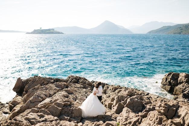 La novia y el novio se abrazan en la playa rocosa de la isla mamula, cerca de la fortaleza de arza