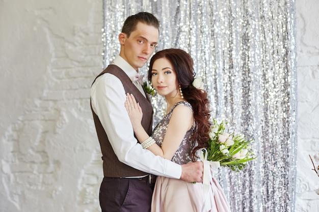 La novia y el novio abrazan y posan para la boda.