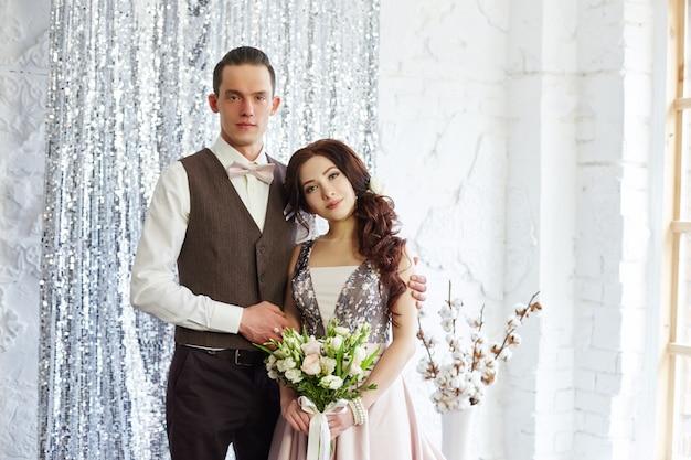 La novia y el novio se abrazan y posan para la boda