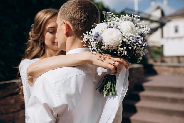 La novia y el novio se abrazan tiernamente caminando por el casco antiguo