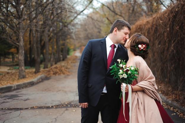 Novia y el novio abrazando en un bosque en el bosque de otoño