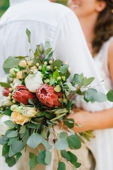 La novia y el novio abrazando a la novia con ramo de rosas proteas y eucalipto en su mano