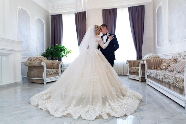 Novia y el novio abrazando suavemente en el interior en un elegante interior. concepto de escarda