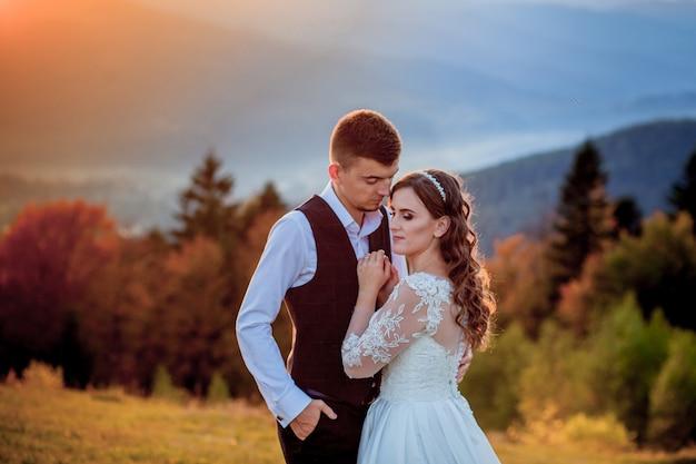 Novia y el novio al atardecer pareja casada romántica