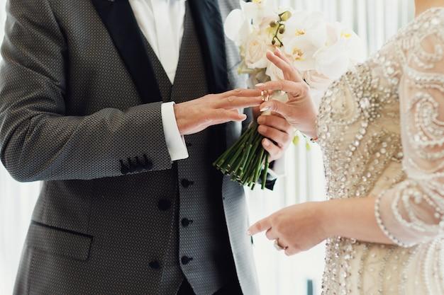 Novia y novio con anillo de bodas y ramo de flores frescas