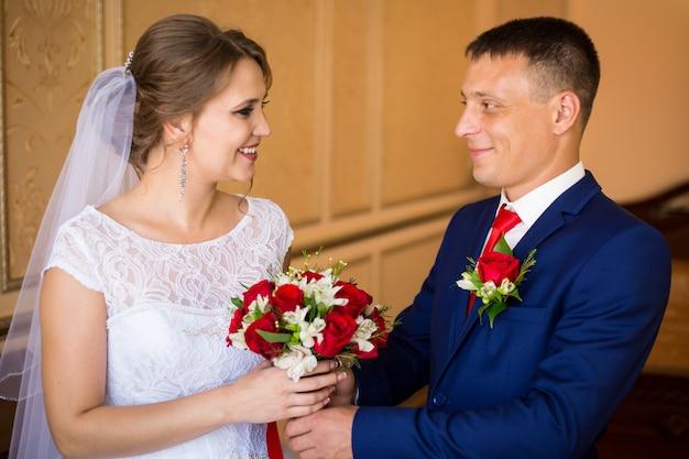La novia y el novio besándose en la habitación del hotel, sosteniendo un ramo de novia