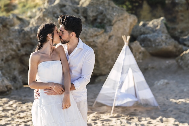 La novia y el novio besándose en la playa.