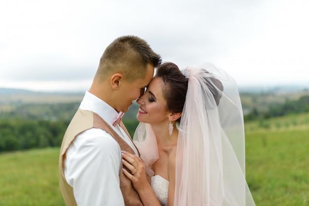 La novia y el novio en una boda a pie. amorosa pareja abrazos y mirarse a los ojos. de cerca.