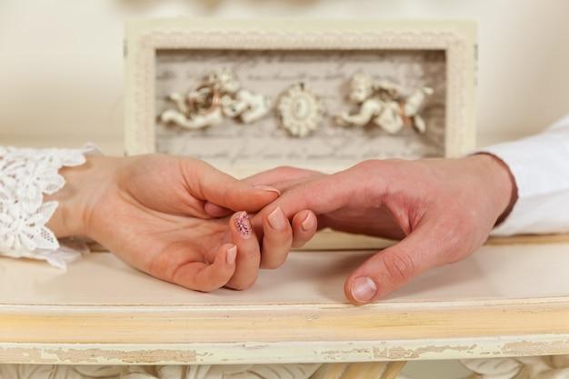Novia y el novio, boda, primer plano de dos manos con el telón de fondo de los ángeles.