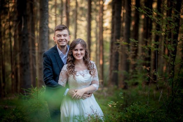 Novia y el novio en el bosque en su boda, sesión de fotos.