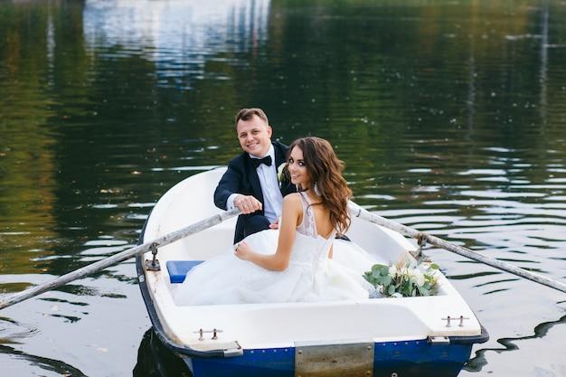 La novia y el novio en un bote de remos en el lago