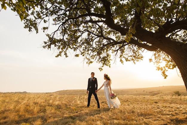 La novia y el novio caminan al atardecer.