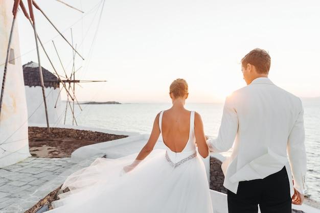 La novia y el novio caminan hacia la puesta de sol sobre el mar