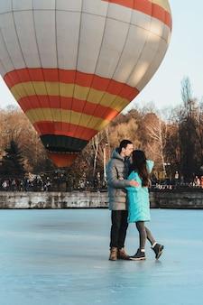 La novia y el novio en el contexto de un lago congelado y un globo volando en un parque de la ciudad.
