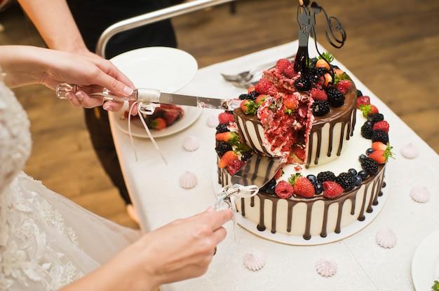 La novia y el novio cortan el pastel de bodas de chocolate.