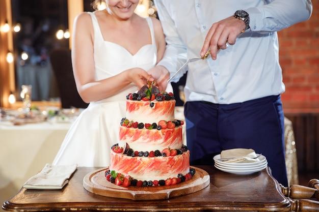 La novia y el novio cortan el pastel de bodas con muchas frutas diferentes y bayas silvestres en la parte superior