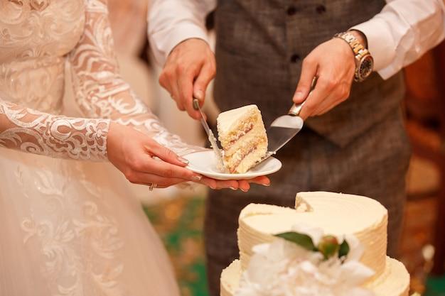 La novia y el novio cortan el pastel de bodas