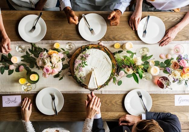Novia y novio corte pastel en recepción de boda