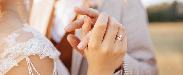 La novia y el novio en el día de la boda se abrazan y muestran amor al atardecer
