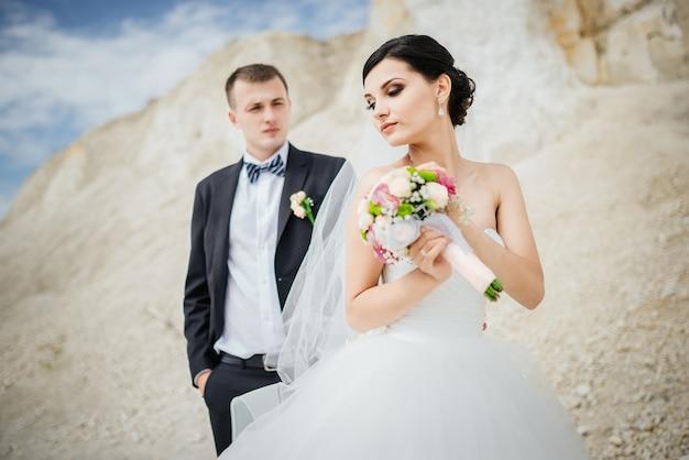 Novia y el novio en el día de la boda caminando al aire libre cerca de la montaña de arena volcánica.