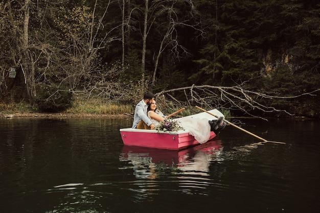 La novia y el novio encantadores se sientan juntos en barco rosado en el lago.