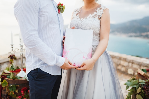 La novia y el novio están abrazados y sosteniendo un certificado de matrimonio en sus manos closeup