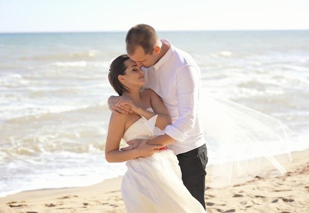 La novia y el novio están apoyados uno al otro de un paisaje de mar