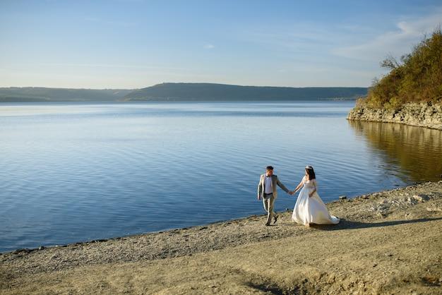 La novia y el novio están caminando cerca del lago en la orilla