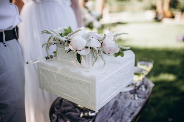Una novia y un novio están cortando su hermoso pastel de bodas. luz de nicel concepto de boda