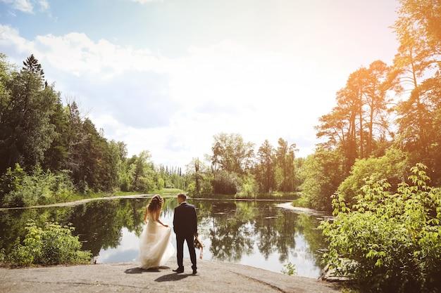 La novia y el novio están en el lago.