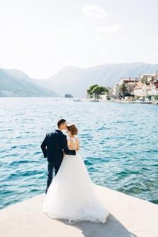 La novia y el novio están de pie abrazándose y besándose en el muelle cerca del casco antiguo de perast back