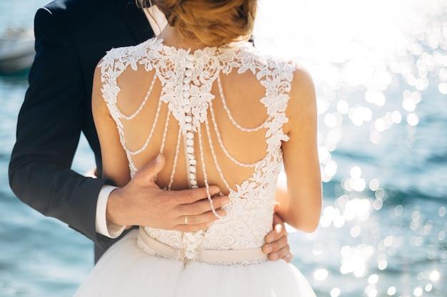 La novia y el novio están de pie y abrazándose en el muelle cerca de la mano del novio en el mar en novias
