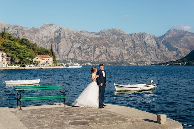 La novia y el novio están de pie ang abrazados en el muelle cerca del casco antiguo de perast cerca de green